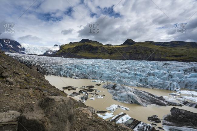 Scenic view of svinafellsjokull glacier against cloudy sky at skaftafell national park, iceland