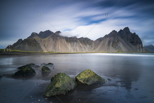 Scenic view of vestrahorn mountain range reflecting on ocean at stokksnes, iceland