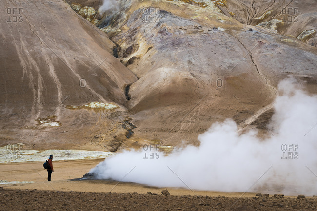 Side view of young man standing by steaming fumarole in geothermal area, namafjall hverir, northern iceland