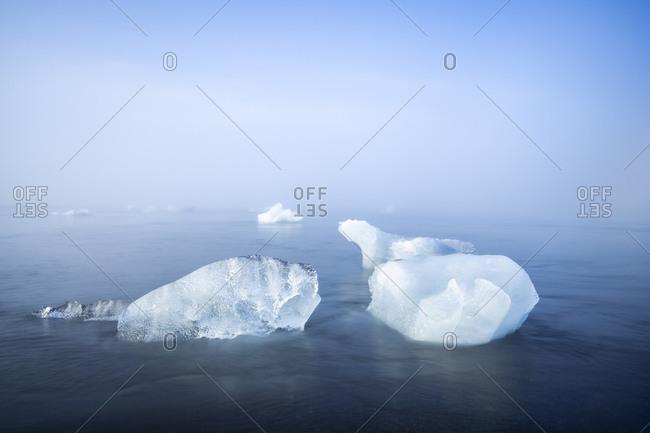 Two chunks of ice on sea shore at diamond beach near jokulsarlon glacier lagoon in foggy weather, iceland