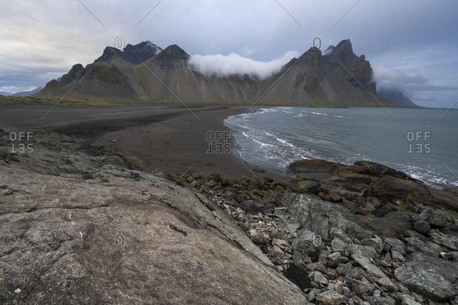 Scenic view of vestrahorn mountain range by sea against cloudy sky at stokksness, iceland