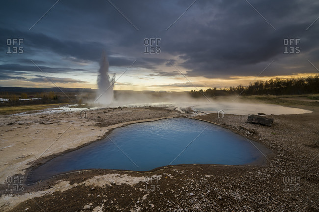Scenic view of blue pond on geothermal area with geyser strokkur erupting in background, geysir, iceland