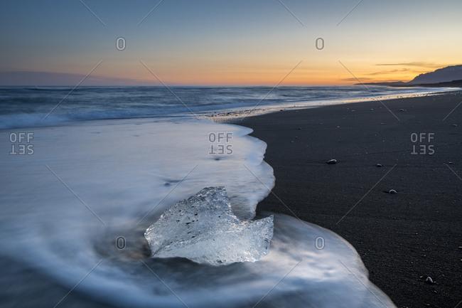 Chunk of ice on sea shore at diamond beach near jokulsarlon glacier lagoon at sunset, iceland