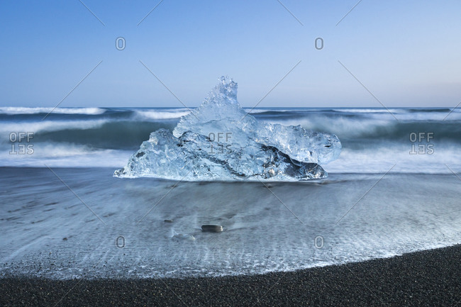 Chunk of ice on sea shore at diamond beach near jokulsarlon glacier lagoon, iceland