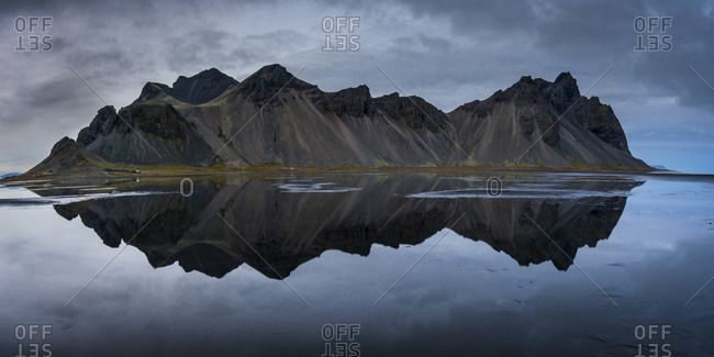 Reflection of vestrahorn mountain range on ocean at stokksnes, iceland