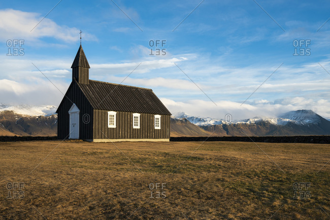 Black wooden budakirkja church against snowcapped mountains, budir, snaefellsness peninsula, iceland