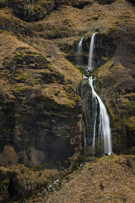 Detail shot of waterfall cascading on hill, south iceland