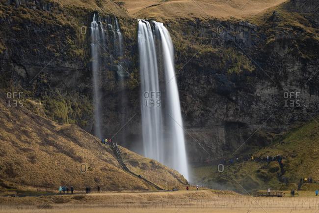 Tourists at seljalandsfoss waterfall, south iceland