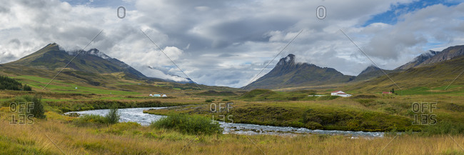 Panoramic shot of farms and mountains against cloudy sky, northern iceland, iceland, europe