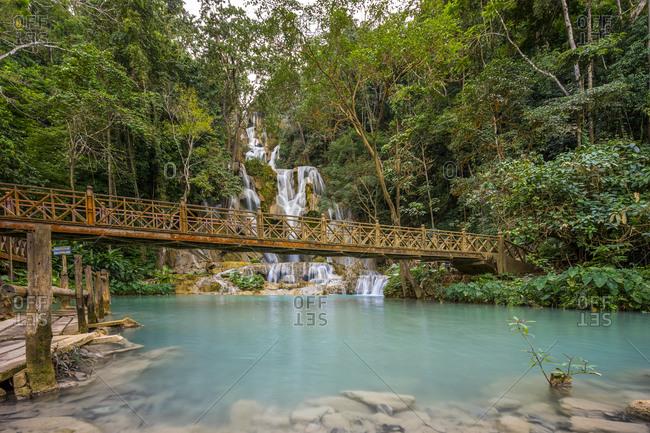 Wooden bridge over river against kuang si waterfalls, luang prabang, laos