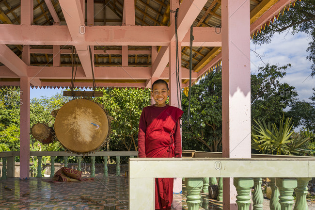 Luang namtha, luang namtha province, laos - january 30, 2017: smiling buddhist monk standing next to gong on terrace of monastery in luang namtha province, laos