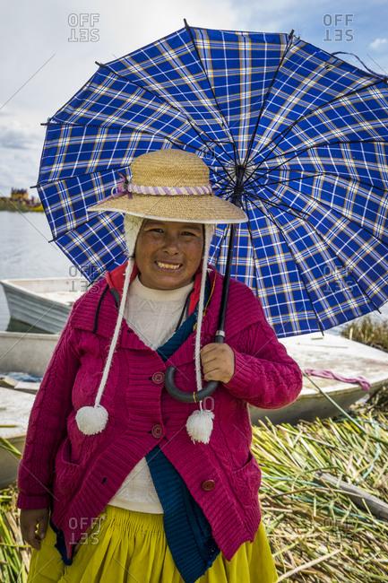 Puno, puno, peru - april 23, 2017: portrait of smiling woman dressed in traditional clothing holding umbrella, uros islands, lake titicaca, peru
