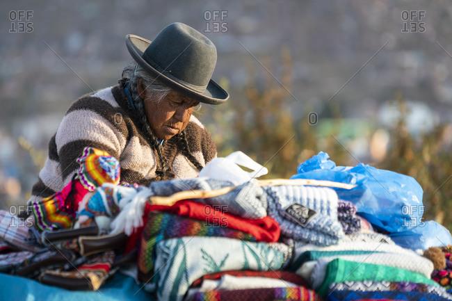 Cusco, cusco, peru - october 7, 2018: senior female vendor selling sweaters, cusco, peru