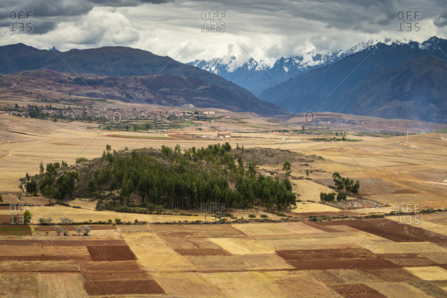 Fields in sacred valley with andes mountains in background, peru