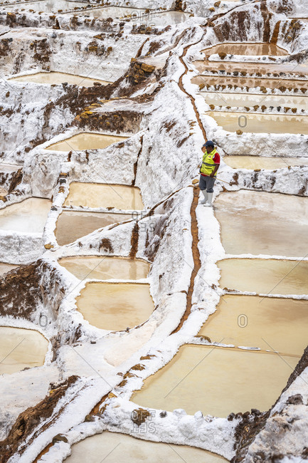 Maras, cusco, peru - october 8, 2018: man working at salineras de maras, sacred valley, peru