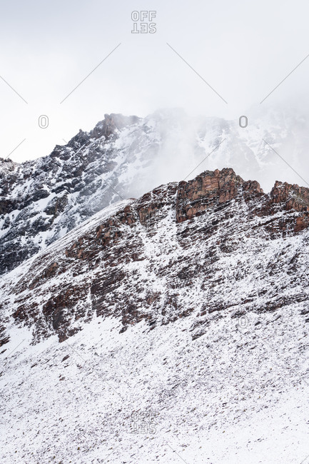 Snowcapped mountain peaks in the andes covered with fog, rainbow mountain trail, pitumarca, peru