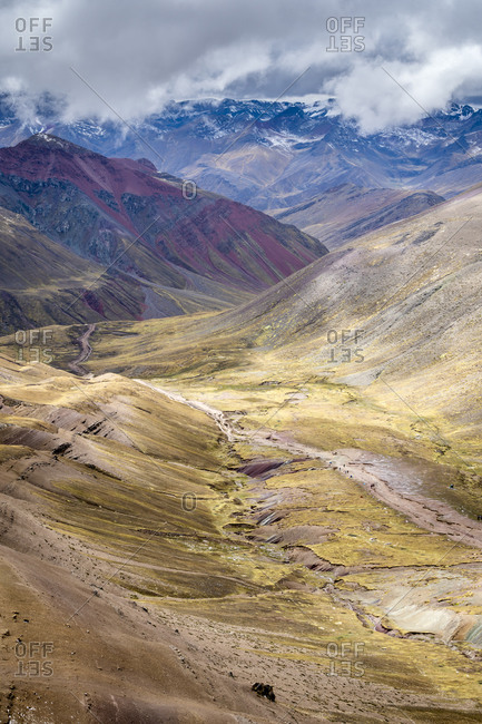 Scenic view of valley amongst high andes mountains on rainbow mountain trail, pitumarca, peru