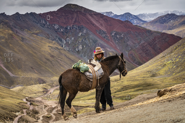 Pitumarca, cuzco, peru - october 13, 2018: horseman standing by horse on rainbow mountain trail with high andes mountain in background, pitumarca, peru