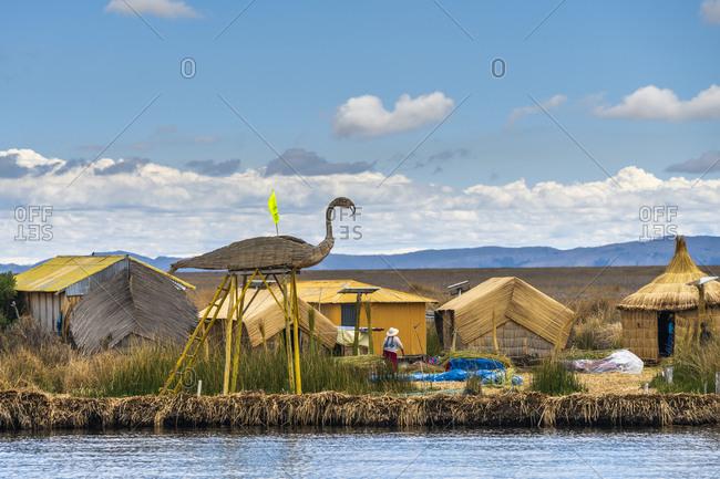 Houses made of reed and flamingo like high seat at uros islands, lake titicaca, peru