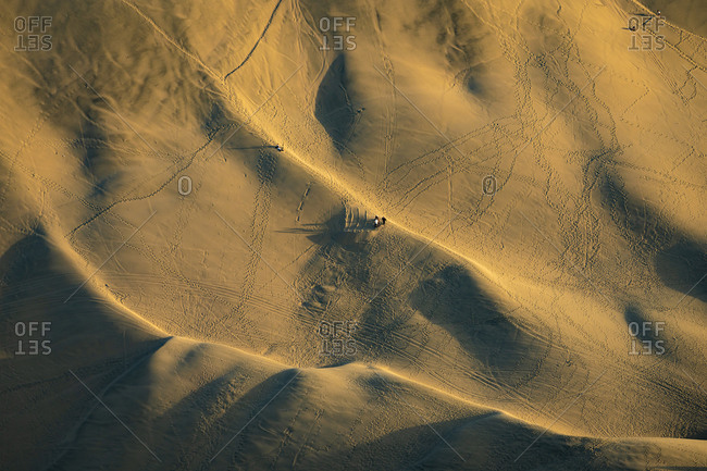 Aerial view of people sandboarding in dunes by huacachina oasis, ica,