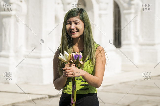 Mandalay, mandalay region, myanmar (burma) - january 12, 2018: smiling young woman dressed in green casuals holding flowers in front of kuthodaw pagoda, mandalay, myanmar