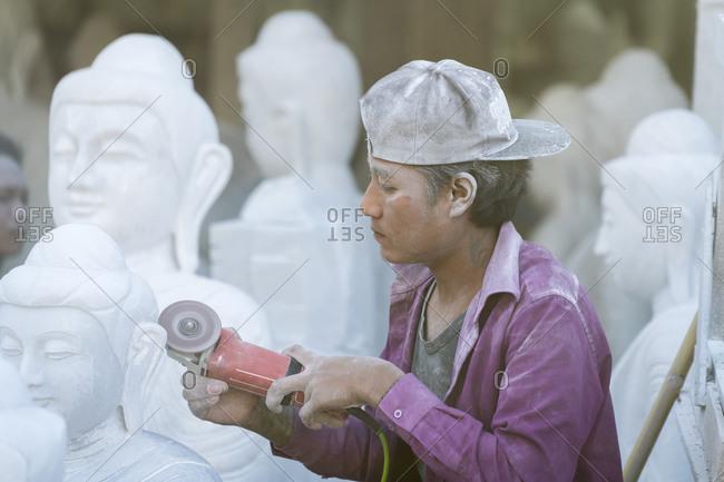Mandalay, mandalay region, myanmar (burma) - january 12, 2018: young marble carver carving buddha statue, mandalay, myanmar