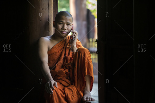 Mandalay, mandalay region, myanmar (burma) - january 12, 2018: buddhist monk dressed in saffron robe talking through mobile phone while sitting at window of monastery, mandalay, myanmar