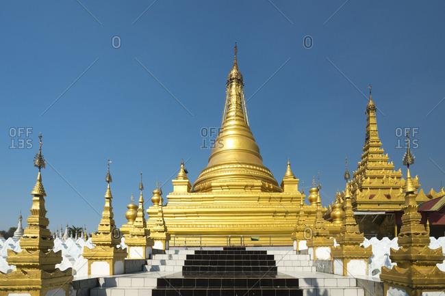 Golden sanda muni pagoda against clear blue sky, mandalay, myanmar