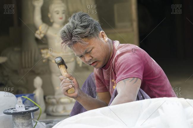 Mandalay, mandalay region, myanmar (burma) - january 12, 2018: marble carver using hammer while carving buddha statue, mandalay, myanmar