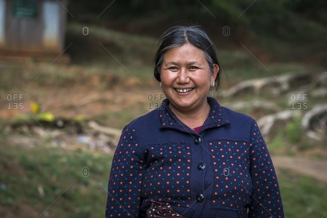 Hsipaw, shan, myanmar (burma) - january 15, 2018: smiling mature woman of palong tribe standing outdoors, near hsipaw, myanmar