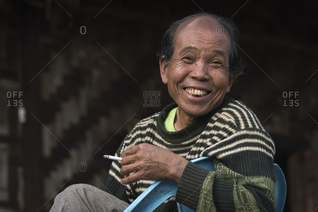 Hsipaw, shan, myanmar (burma) - january 15, 2018: cheerful burmese man of palong tribe smoking cigarette while sitting outdoors, near hsipaw, myanmar