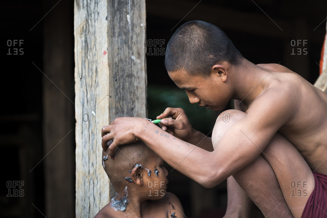 Hsipaw, shan, myanmar (burma) - january 15, 2018: young monk shaving hair on head of novice monk with razor, near hsipaw, myanmar