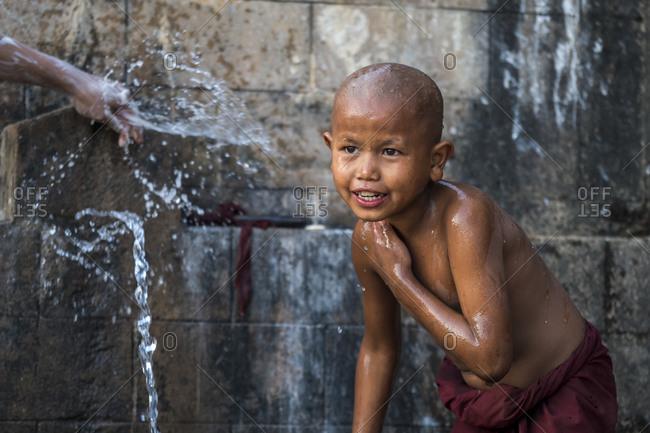 Hsipaw, shan, myanmar (burma) - january 15, 2018: novice shirtless monk bathing under running water outdoors, near hsipaw, myanmar