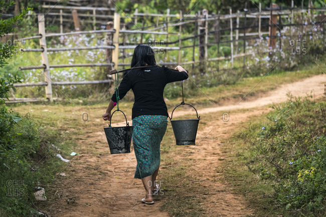 Rear view of woman carrying buckets of water using bamboo stick in palong village, near hsipaw, myanmar