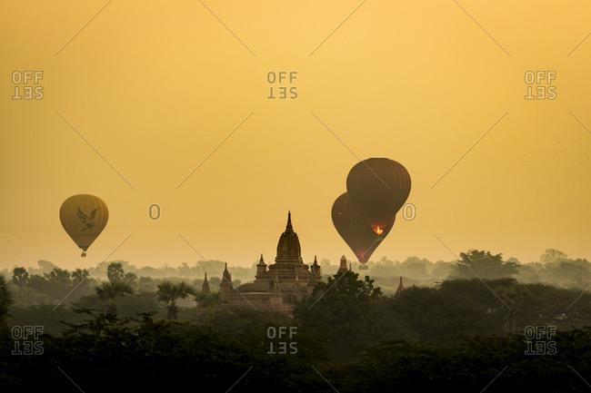 Old bagan, mandalay region, myanmar (burma) - january 18, 2018: hot air balloons flying near pagoda during sunrise, unesco, bagan, myanmar