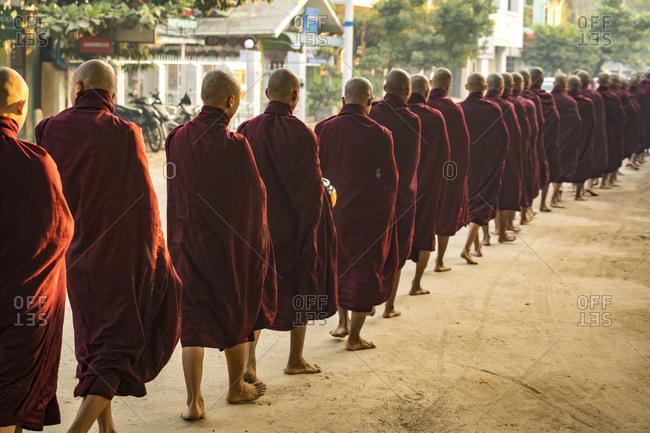 Nyaung-u, mandalay region, myanmar (burma) - january 18, 2018: rear view of monks in queue on street receiving alms, nyaung u, myanmar