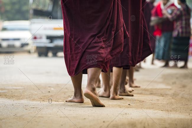 Detail shot of feet of monks waiting in queue while receiving alms, nyaung u, myanmar