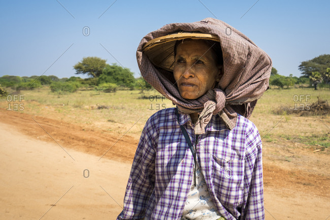 Old bagan, mandalay region, myanmar (burma) - january 18, 2018: portrait of senior woman with thanaka on face wearing scarf during sunny day, bagan, myanmar
