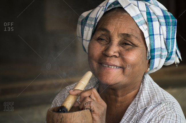 Old bagan, mandalay region, myanmar (burma) - january 18, 2018: smiling woman smoking thick burmese cigar, bagan, myanmar