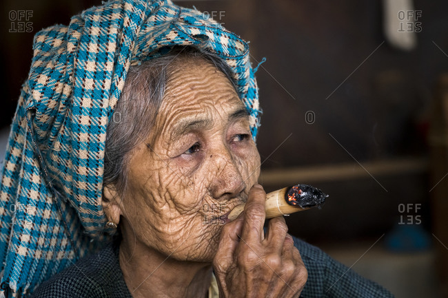 Old bagan, mandalay region, myanmar (burma) - january 18, 2018: contemplated senior burmese woman smoking cigar, bagan, myanmar