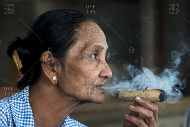Old bagan, mandalay region, myanmar (burma) - january 18, 2018: thoughtful senior burmese woman smoking cigar, bagan, myanmar