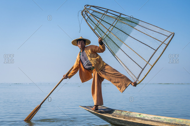 Nyaungshwe, shan, myanmar (burma) - january 20, 2018: intha fisherman posing with typical conical fishing net on boat against clear blue sky, lake inle, nyaungshwe, myanmar