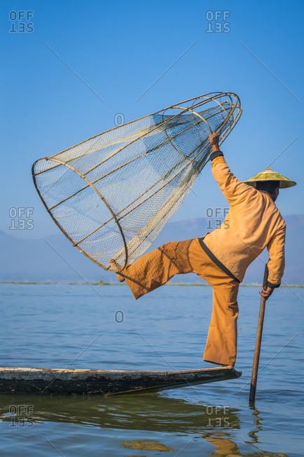 Nyaungshwe, shan, myanmar (burma) - january 20, 2018: rear view of intha fisherman posing with typical conical fishing net on boat against clear blue sky, lake inle, nyaungshwe, myanmar