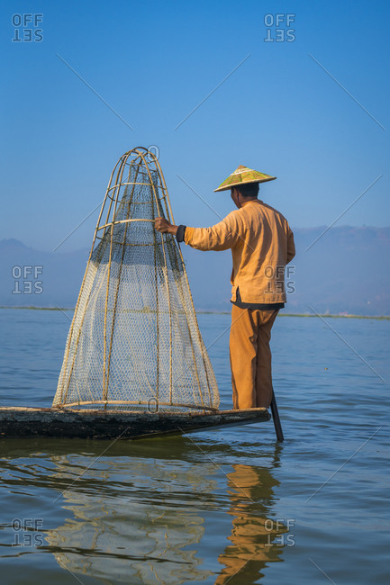 Nyaungshwe, shan, myanmar (burma) - january 20, 2018: rear view of intha fisherman standing with typical conical fishing net on boat against clear blue sky, lake inle, nyaungshwe, myanmar