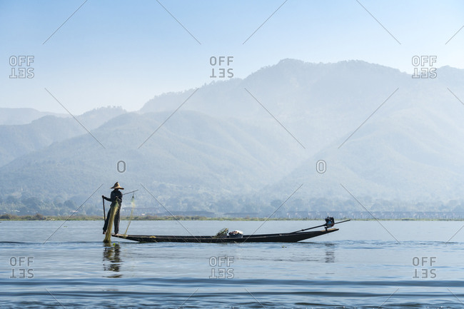 Nyaungshwe, shan, myanmar (burma) - january 20, 2018: fisherman using fishing net on boat against mountains, lake inle, nyaungshwe, myanmar