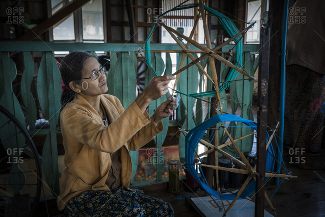 Nyaungshwe, shan, myanmar (burma) - january 20, 2018: senior burmese woman winding up threads in textile workshop, lake inle, myanmar
