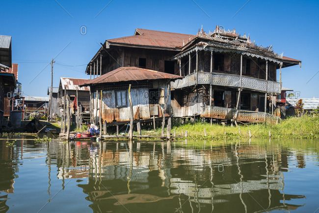 Nyaungshwe, shan, myanmar (burma) - january 20, 2018: woman washing clothes by stilt house at lake inle, myanmar