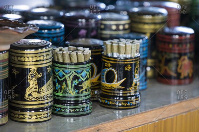 Burmese cigars in colorful painted containers on display in cheroot workshop, lake inle, myanmar