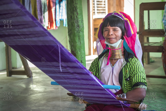 Nyaungshwe, shan, myanmar (burma) - january 20, 2018: portrait of burmese woman from kayan tribe weaving at textile workshop, lake inle, myanmar