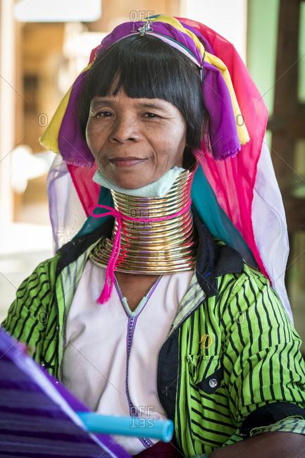 Nyaungshwe, shan, myanmar (burma) - january 20, 2018: portrait of burmese woman from kayan tribe weaving at textile workshop